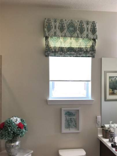 Valance and fabric roman shade in bathroom window