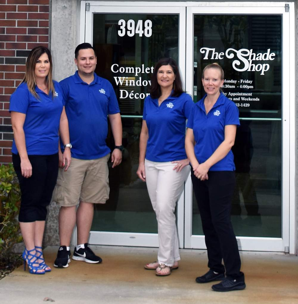 Staff Photo , three women and one man wearing blue shirts